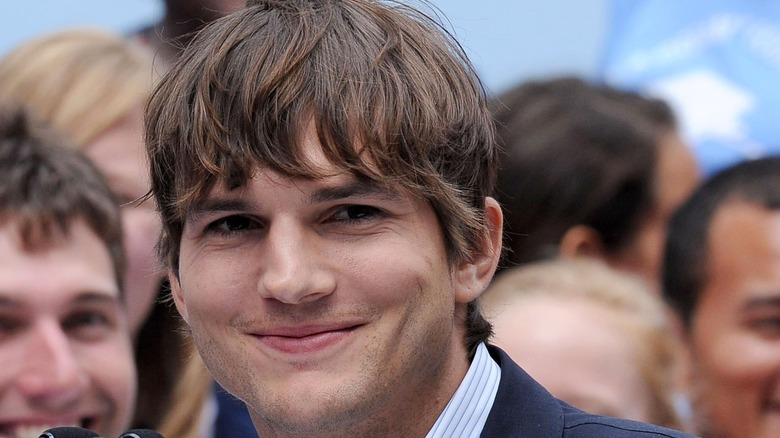 Ashton Kutcher smiles for the camera at an event.