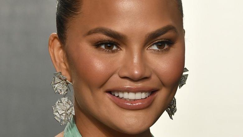 Chrissy Teigen smiling hair back and statement earrings