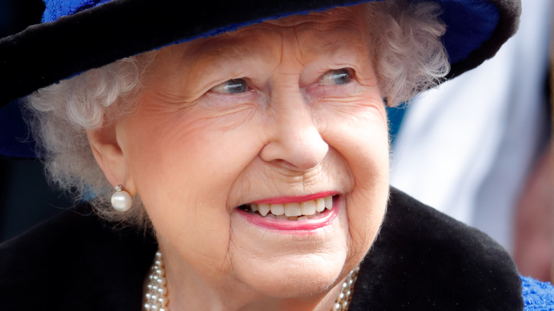Queen Elizabeth smiling in a blue outfit and hat