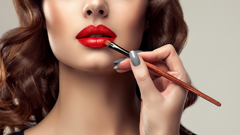 Woman uses brush to apply red lipstick