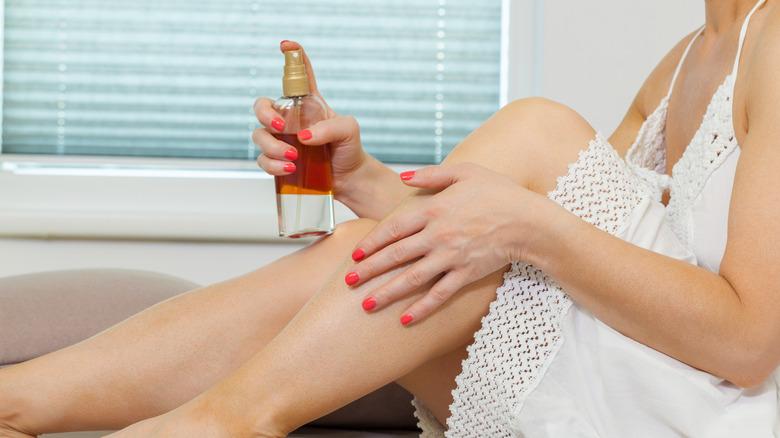 Woman applying self tanner to legs