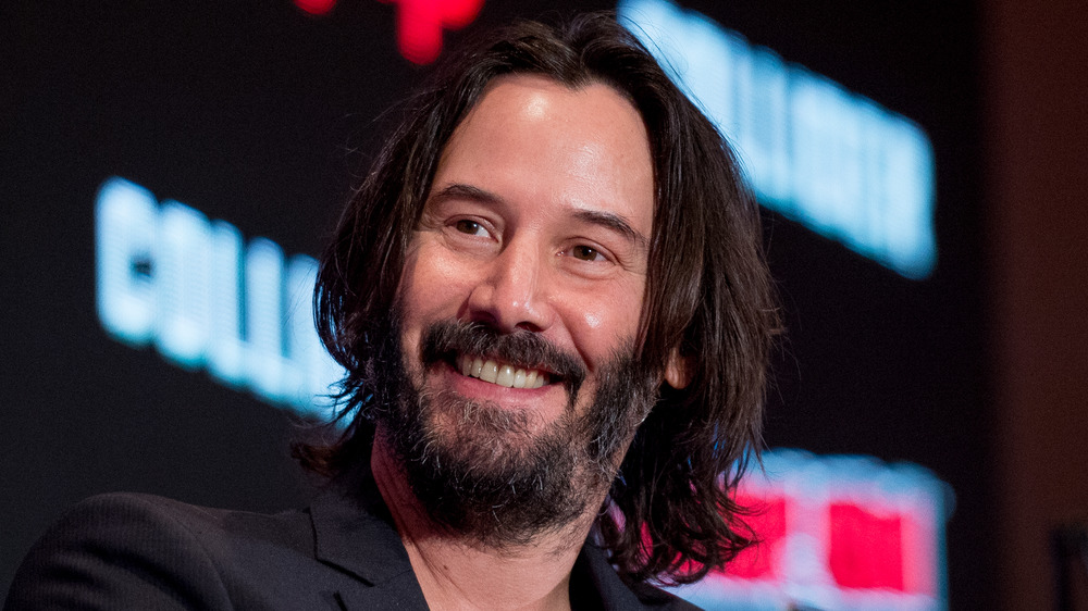 Keanu Reeves smiling at a panel event
