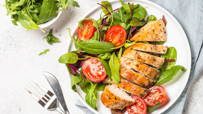 A plate of chicken and salad with an accompanying bowl of greens