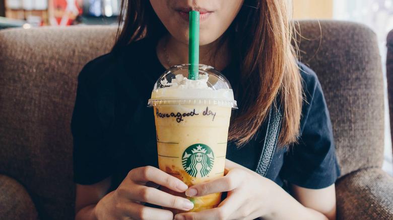 Woman drinking orange Frappuccino