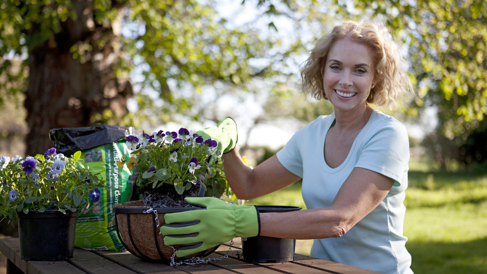 A woman smiling while gardening