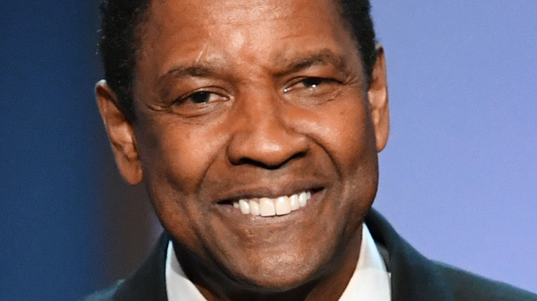 Denzel Washington smiles onstage at an event
