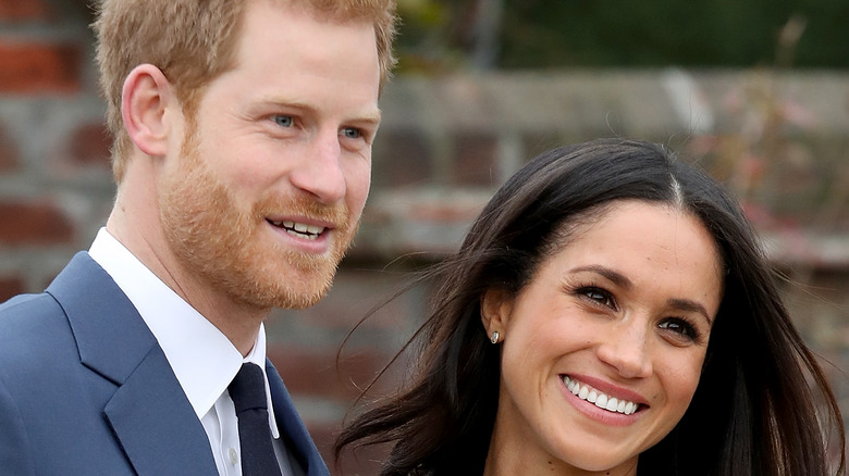 Meghan and Harry smile for photographers