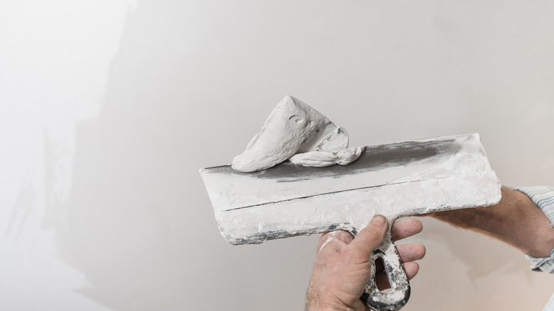Construction worker with white mud on a spatula with drywall in the background.