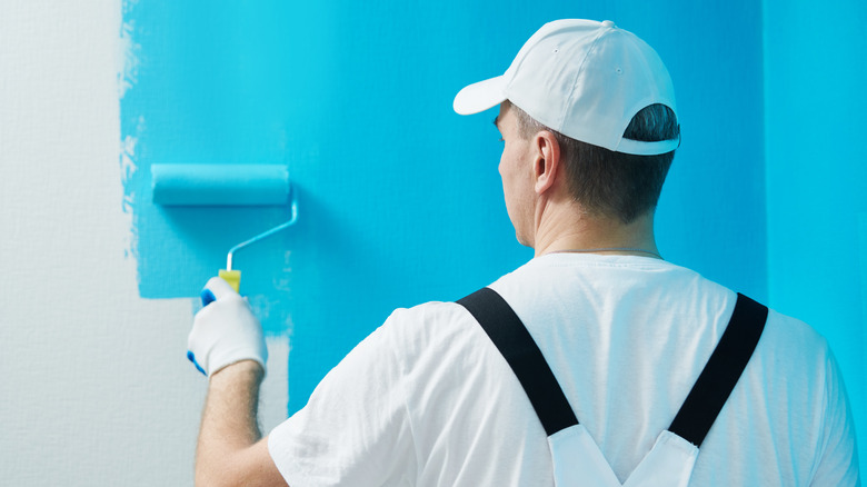 Man wearing white facing a wall and painting it blue with a paint roller.