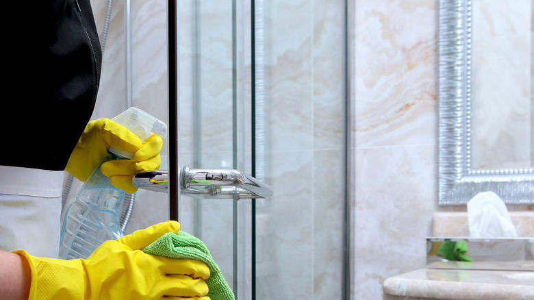 Woman wearing yellow gloves cleaning a shower