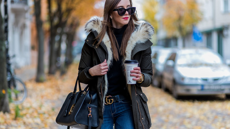 Woman in a Gucci belt, parka, and sunglasses