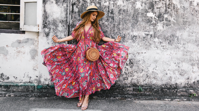 Woman in maxi dress in front of a gray wall