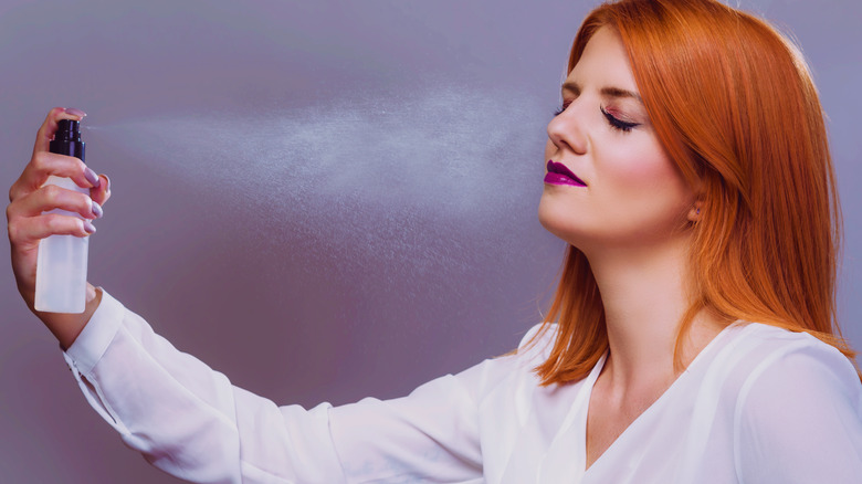 Woman setting her makeup with spray