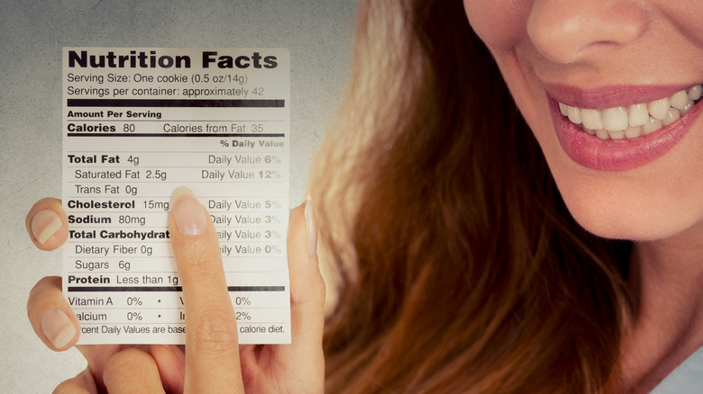 Smiling woman holding a nutrition facts label pointing to Trans Fat.