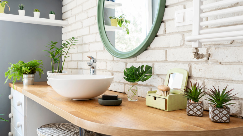 white modern bathroom with raised sink and wood countertop