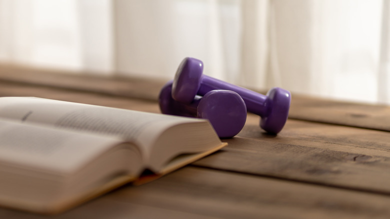 Dumbbells next to a book