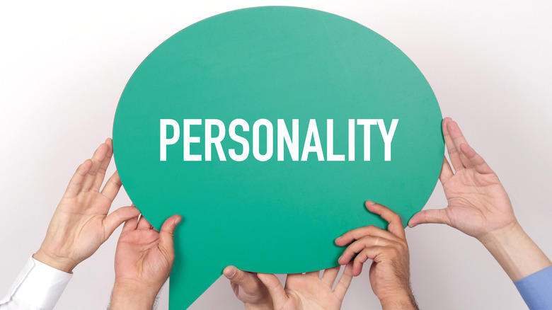 Men's hands holding a green sign that says 'personality.'