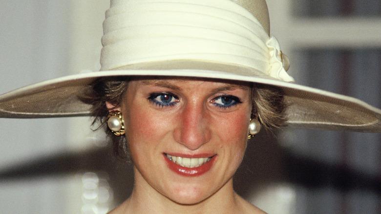 Princess Diana wearing a white hat.