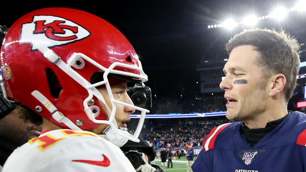 Tom Brady and Patrick Mahomes in helmet talking post Super Bowl