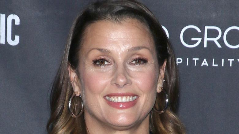 Bridget Moynahan smiling with gold hoop earrings