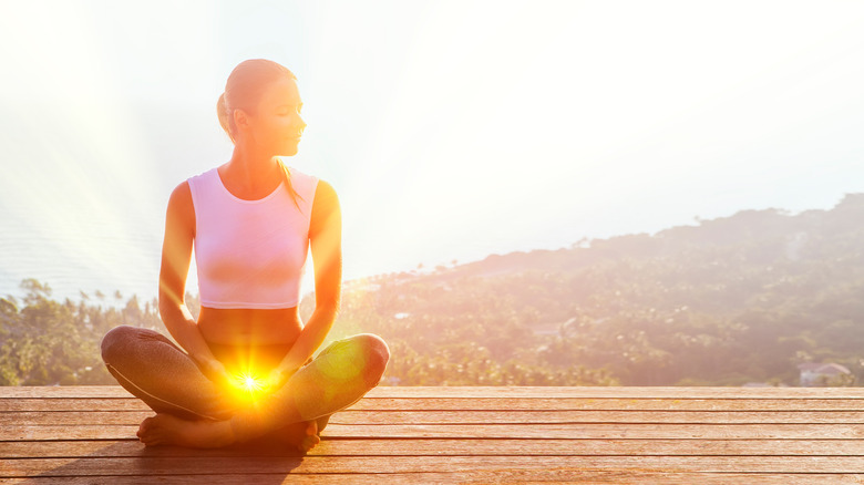 A woman sitting in lotus position with her sacral chakra lit up