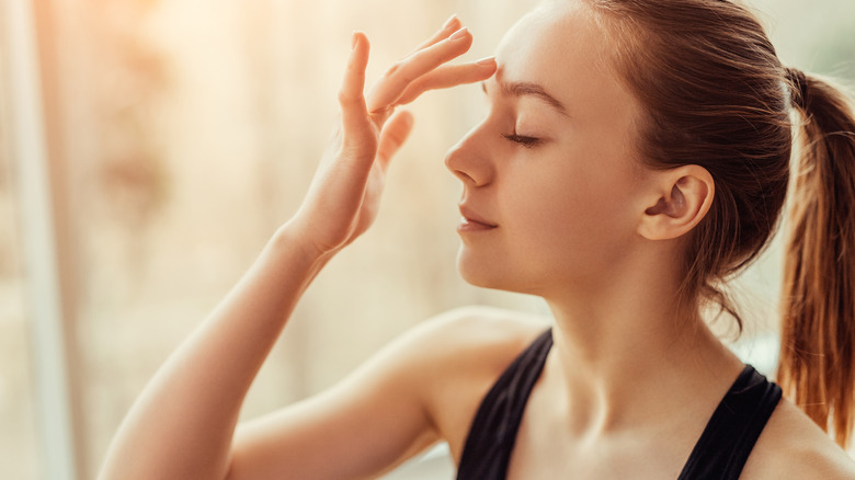 A woman touching her third eye area