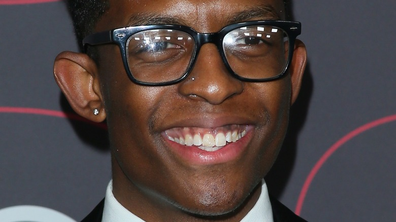 Breland smiles with glasses and stud earrings