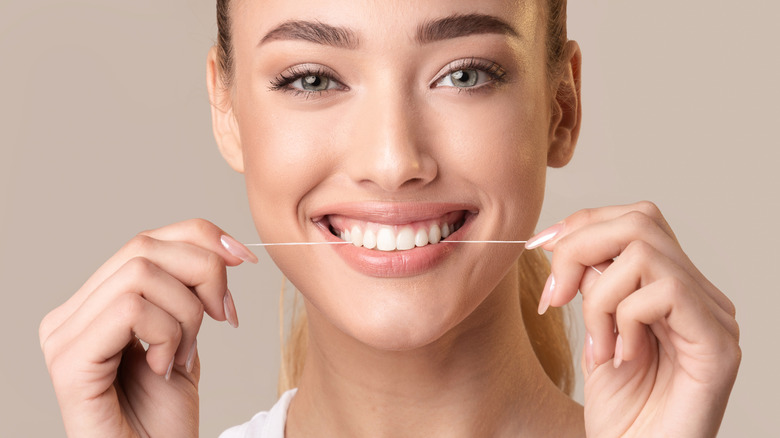 woman smiling and flossing teeth