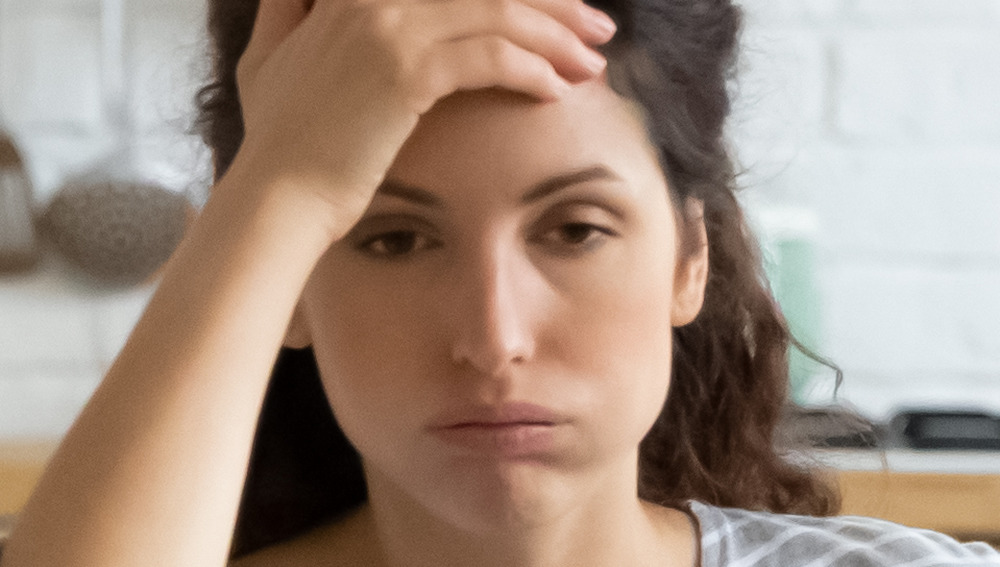 A woman holding her head and looking distressed