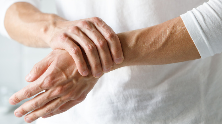 Male hand holding wrist