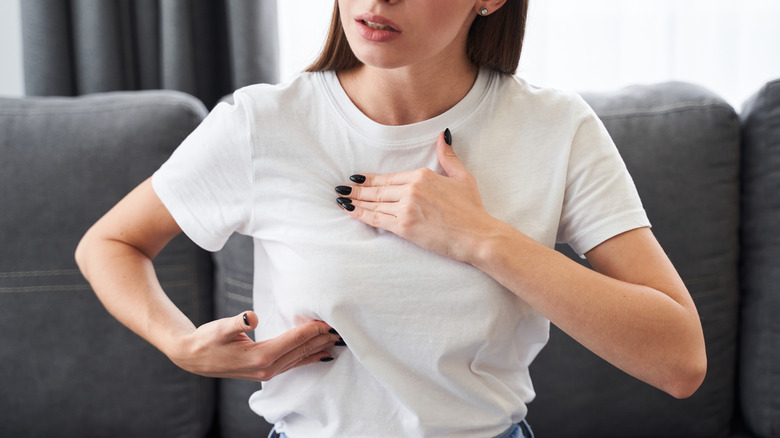Woman in white t-shirt checking her breast