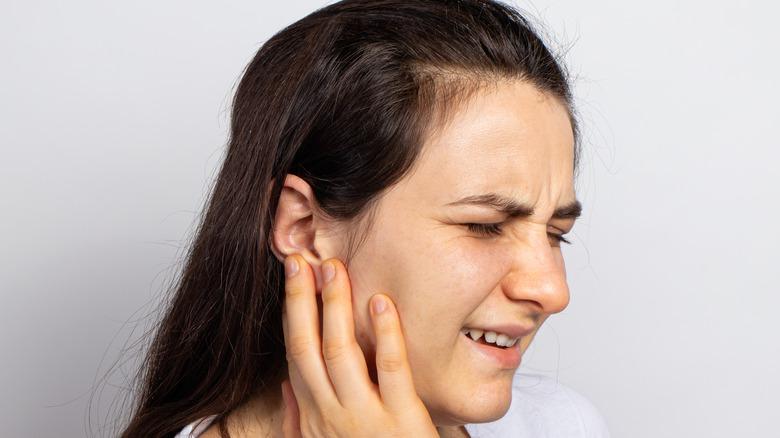 Woman touching her ear