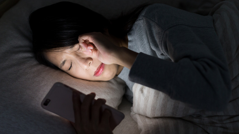 Woman laying in bed rubbing eyes while using mobile phone