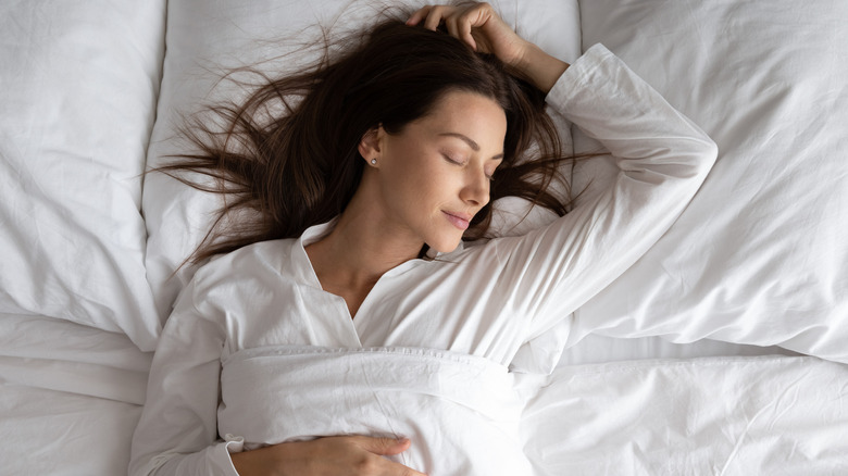 Woman sleeping in all white bedding