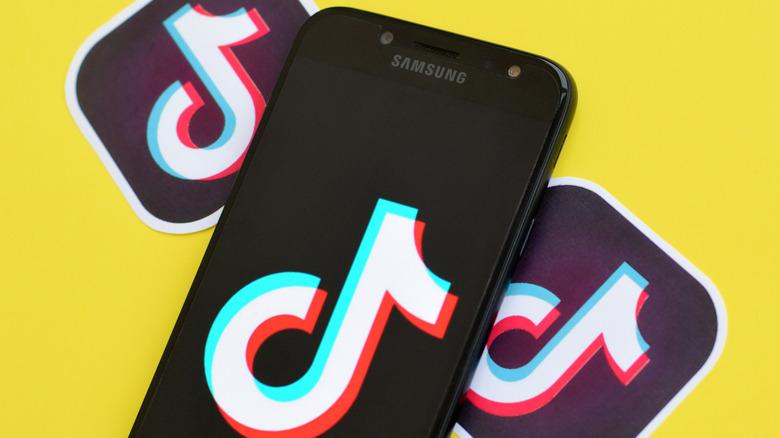 TikTok logos and phone with TikTok logo on a yellow background.