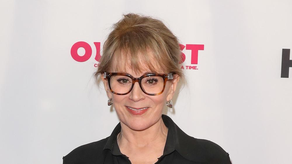 Patricia Richardson smiling with dark rimmed glasses