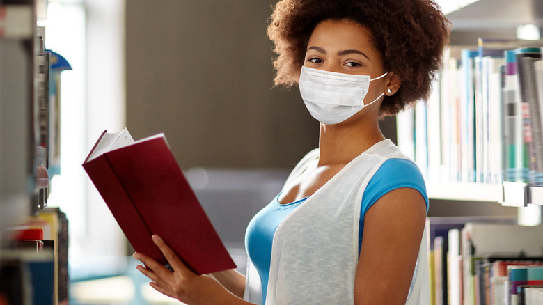 Woman reading in library with facemask