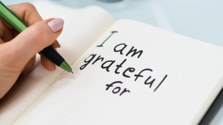 """Woman writing """"I am grateful for"""" in a journal"""