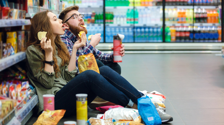 couple eating junk food in store