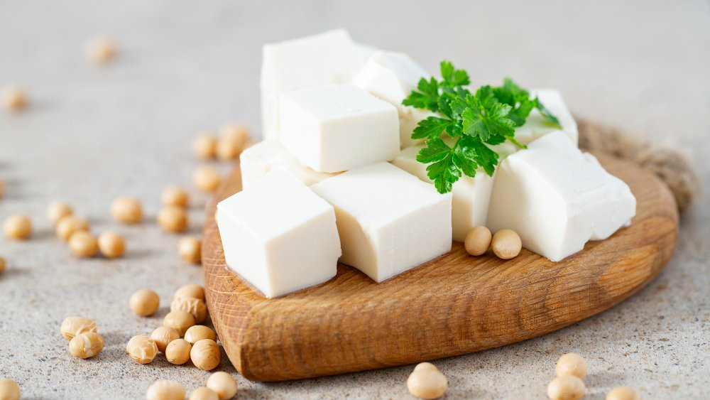 Tofu on a cutting board with herbs and beans