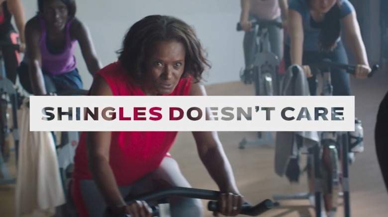 """Woman taking a spin class with the phrase """"Shingles Doesn't Care"""" across the screen"""