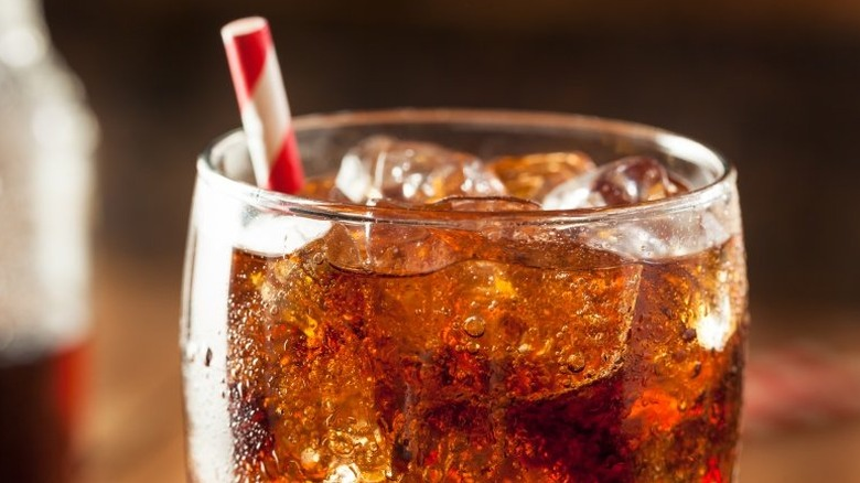 A glass of cola with ice and a straw