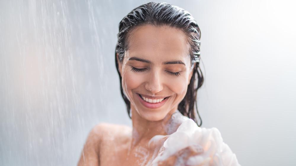 Woman washing body in shower