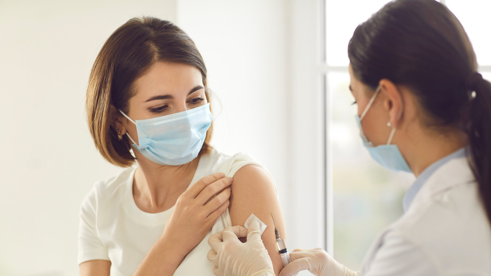 A woman getting vaccinated by her doctor