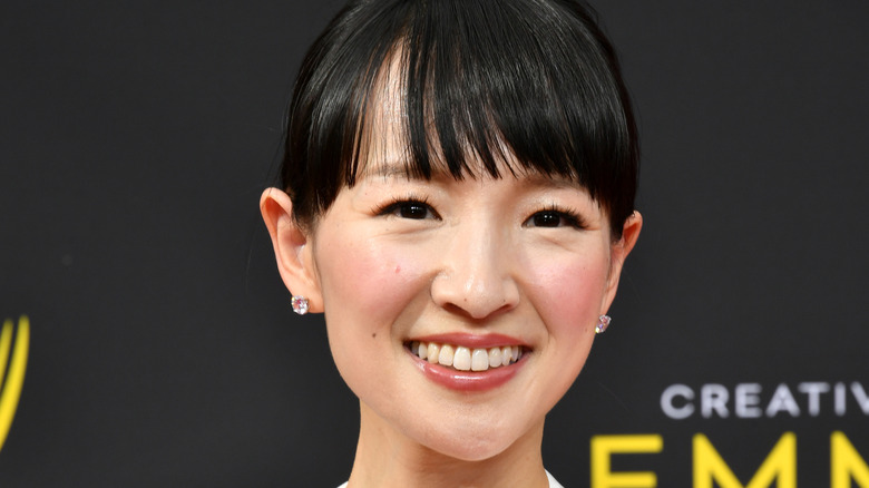 Marie Kondo with short bangs and sparky stud earrings smiles
