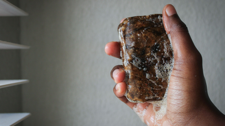 Hand holding bar of black soap