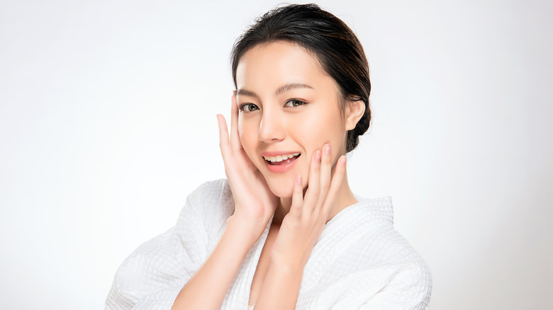 Woman smiling and touching face