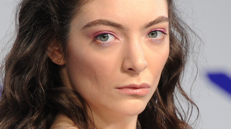 Lorde with serious expression on the red carpet