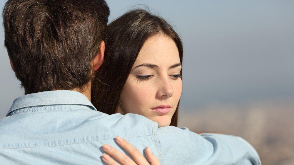 Doubtful woman hugging boyfriend