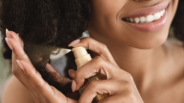 Woman spraying her hair with product